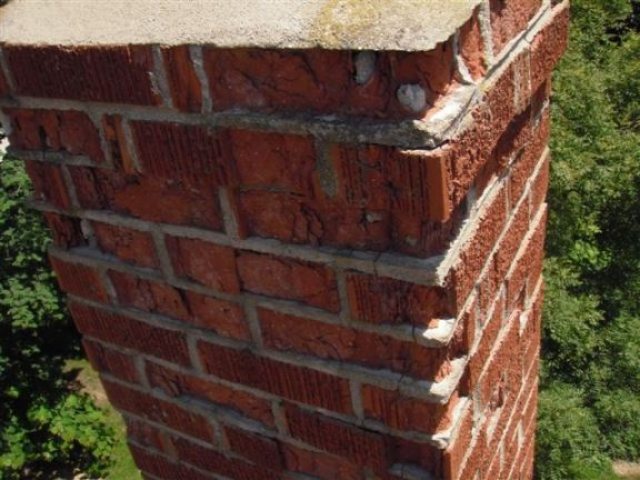 This brick chimney suffers from water damage and is beginning to crumble/spall. Soon it will need to be taken down and replaced.