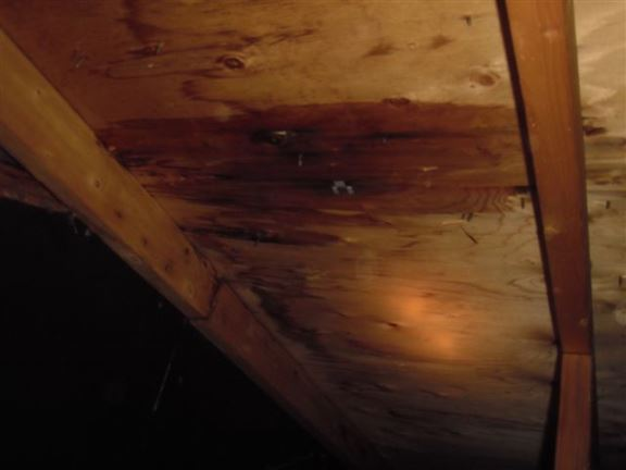 A wet spot on roof sheathing where an upper valley runs onto the roof is a sure sign of shingle or flashing leaks.